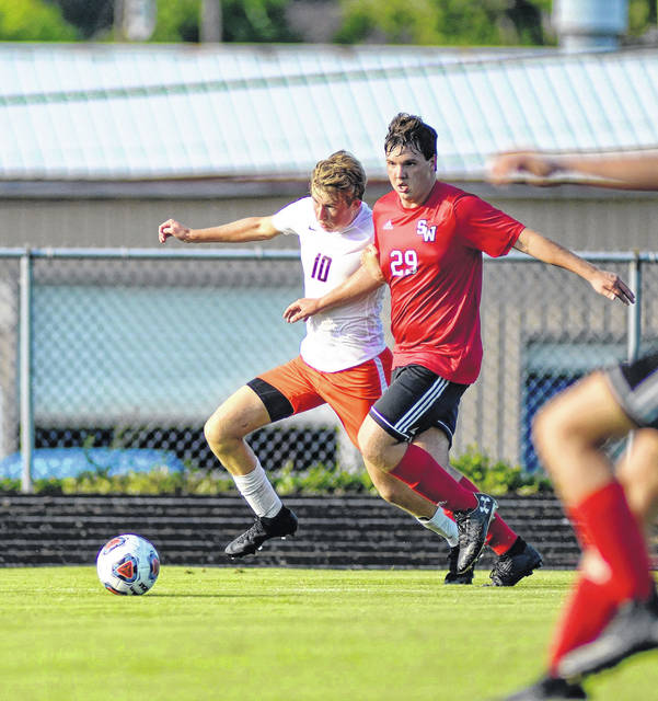 Wheelersburg junior Jackson Schwamburger (10) and South Webster senior Will Collins (29) follow a ball in the corner near Wheelersburg's goal during their meeting in SOC II play on Thursday.
