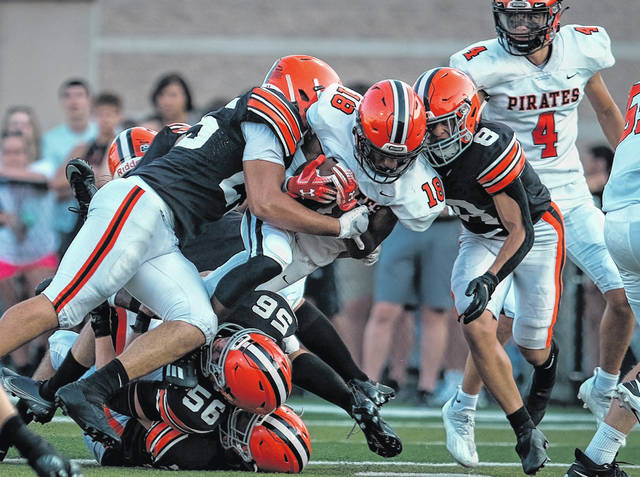 Wheelersburg's Eric Lattimore (18) is tackled by several Ironton defenders, including Blake Murrell (56) and Aiden Young (8), during Friday night's non-league season-opening football game at Ironton's Tanks Memorial Stadium.