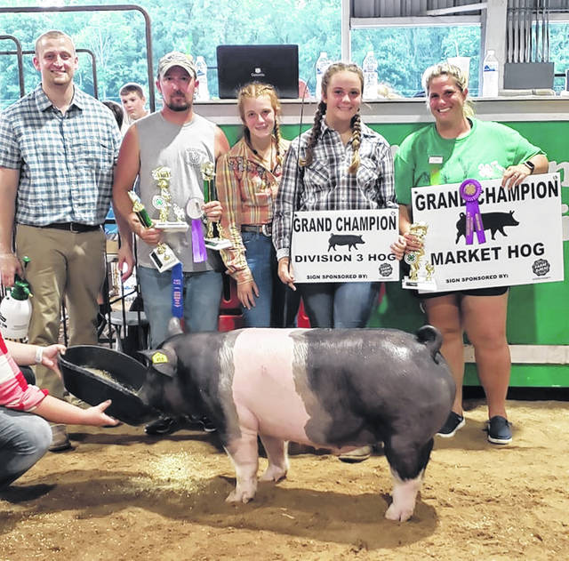 4th from the left is Kaylee Essman with her Grand Champion Hog, along with ther family.