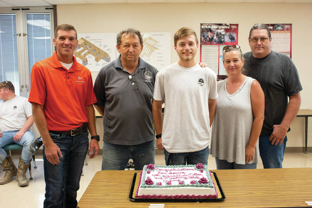 Keith Young, Larry Moore, Eon Spears, Nancy Ellifritt, and Jeff Ellifritt pose together with a cake in celebration of Spears placing 4th in the Nation.