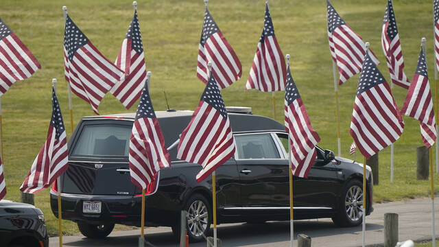 The hearse carrying Navy Corpsman Maxton Soviak leaves Edison High School stadium after his funeral, Monday, Sept. 13, 2021, in Milan, Ohio. Soviak was one of 13 U.S. troops killed in a suicide bombing at Afghanistan's Kabul airport on Aug. 26. (AP Photo/Tony Dejak)