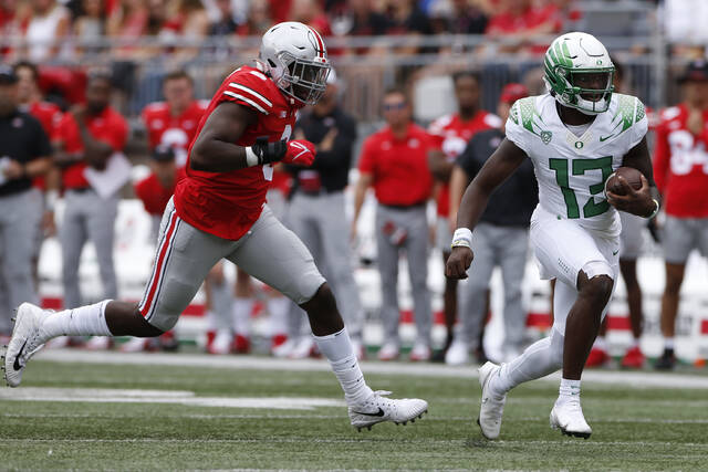 Ohio State defensive lineman Zach Harrison, left, chases Oregon quarterback Anthony Brown during the first half of an NCAA college football game Saturday, Sept. 11, 2021, in Columbus, Ohio. Oregon beat Ohio State 35-28. (AP Photo/Jay LaPrete)