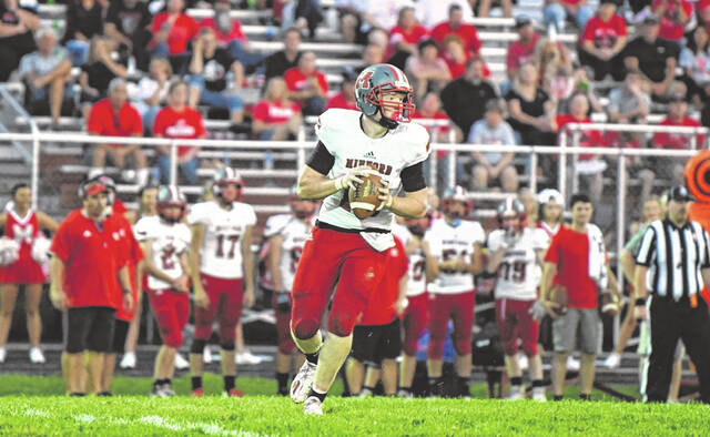 Minford quarterback Devin Parker (15) rolls out to find a Falcon receiver during their 16-14 road win over East Clinton on Saturday night.