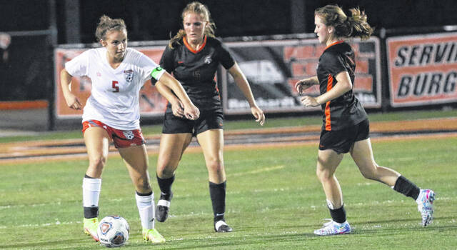 Minford junior Haley Knore (5) tries to keep possession from Wheelersburg defenders Jaelin Thomas (left) and Annie Coriell (right) during Tuesday night's Southern Ohio Conference key girls soccer match.