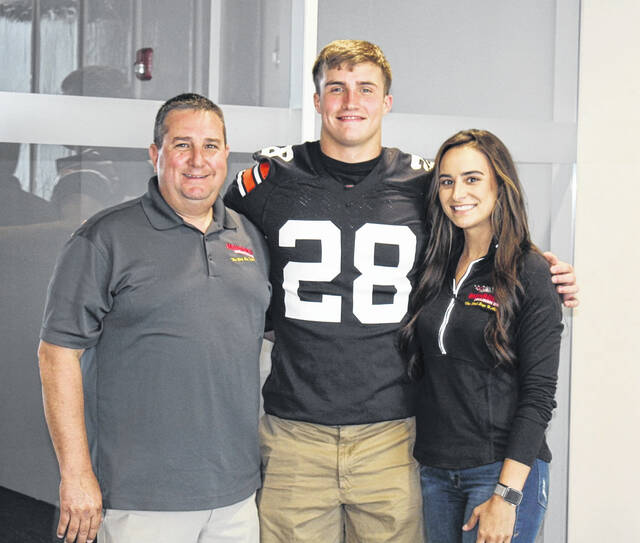 Ohio State freshman linebacker Reid Carrico (center) with Monroe's Collision owners Kevin Monroe (left) and Erin Strickland (right).
