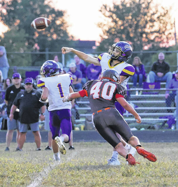 Valley quarterback Carter Nickel (10) throws a pass for a completion as Eastern's Landon Reinsmith (40) rushes in during Friday night's non-league football game at Eastern High School.
