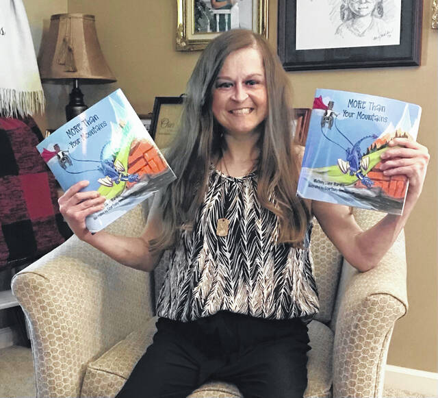 Whitney Lane Ward, author of <em>MORE Than Your </em><em>Mountains</em>, holds her children's picture book in each hand.