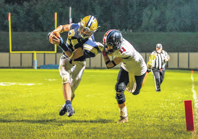 Notre Dame running back Gavin Hart (24) is horse-collar tackled by Rosecrans' Weston Hartman (11) on this touchdown during Saturday night's non-league football game at Spartan Municipal Stadium.