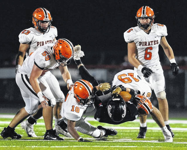 Wheelersburg defenders Eric Lattimore (18) and Casey Doerr (19) tackle an Oak Hill Oaks' ballcarrier as the Pirates' Ethan Royal (59), Josh Boggs (6) and Eli Swords (23) look on during Friday night's Southern Ohio Conference Division II football game at Oak Hill's Davis Stadium.