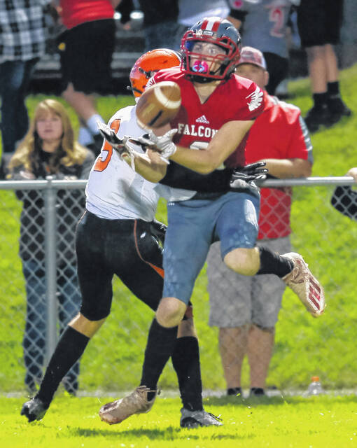 Minford's Trenton Zimmerman (2) makes a reception over a Wheelersburg defender during last Friday night's Southern Ohio Conference Division II football game at Minford High School.