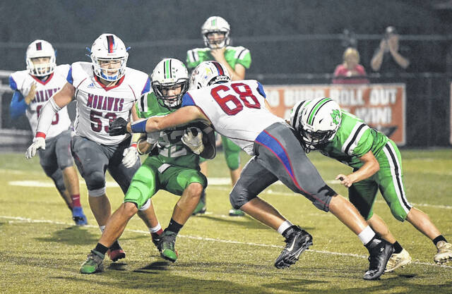 Northwest's Aaron Penn (68) and Alex Baer converge (53) to tackle Green's Nathaniel Brannigan (22) during Saturday night's Southern Ohio Conference Division I football game at Wheelersburg's Ed Miller Stadium.