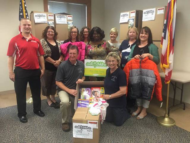Representatives from the four Morrow County school districts and the local food pantry accepted coats, baby clothing and other items Wednesday. In the center is Beverly Robinson, executive director and founder of Coats 4 Children.