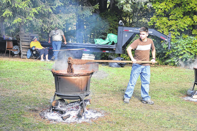 Luke Waldo from Boy Scout Troop 50, Marion, takes his turn stirring apple butter at the Mount Gilead State Park Apple Butter Festival held Saturday. Troop 50 was one of six Boy Scout Troops helping to stir the apple butter in its cooking process.