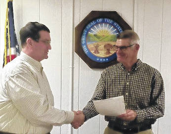 Mount Gilead village council member John Oyster's last meeting was Dec. 18. Here he receives a resolution thanking him for his service to council from Mayor Mike Porter.