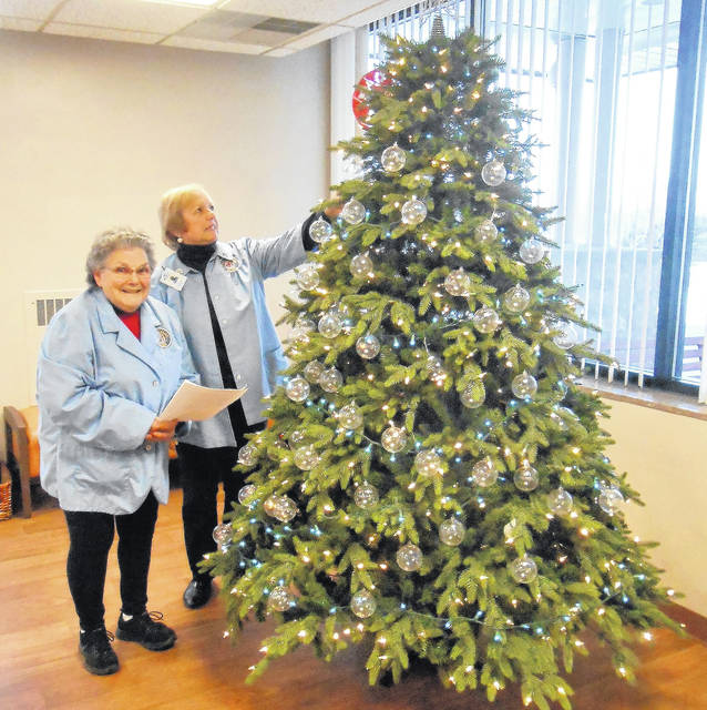 Shirley Dendinger reads from the history of the hospital Remembrance Tree while MCH Auxiliary President Marilyn Schnippel adjusts a bulb on the tree.