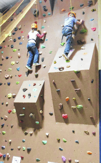 Foster children reach the top of the climbing wall at Heartland Conference Retreat Center.