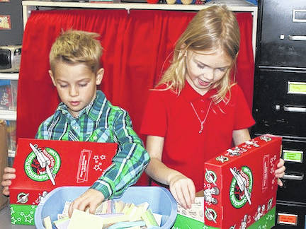 Cardington-Lincoln first grade students Connor VanHoose and Olivia Frank pack shoe boxes to be delivered to children to enjoy in other countries at Christmas.
