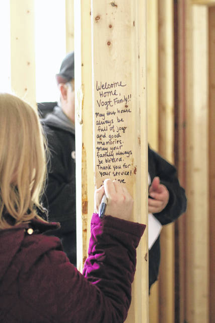 Erin Miller | Galion Inquirer A friend of the Nick Vogt family leaves a message on one of the 2x4 wall studs which will soon be enclosed inside the walls of their new home located on State Route 61 north of Crestline.