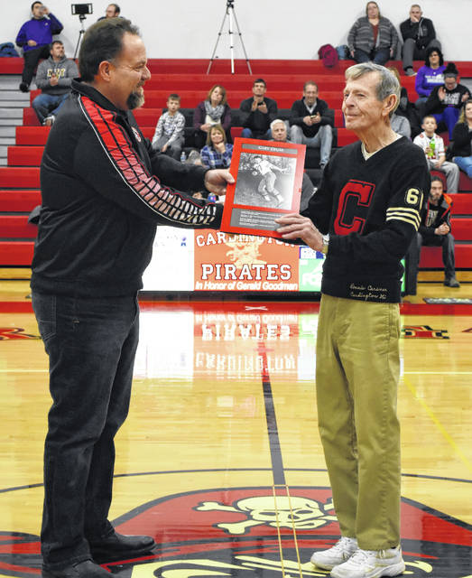 Cardington-Lincoln High School principal Joe Mills (l) presents a plaque recognizing Gary Crum as an inductee into the pre-1976 Athletic Hall of Fame to Crum's brother-in-law Ron Carsner. The ceremony took place Jan. 19 between the reserve and varsity basketball games with East Knox.