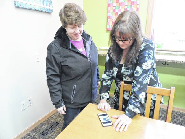 Selover librarian Tammy Keefer shows patron Susan Berthold how to access eBooks on her phone.