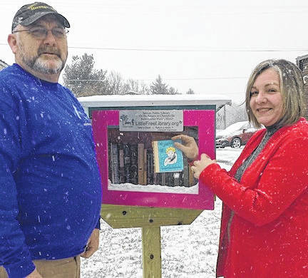 Wayne Hinkle, owner of Hinkle's Marengo Hardware, and Tiffani Hupfer, a Branch Manager with U.S. Bank, with the new Marengo Little Free Library.