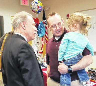 Judge Robert Hickson, left, visits with John Stinehelfer and his granddaughter.
