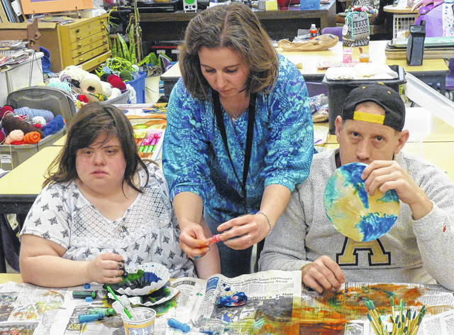 Making butterflies for the window display at Keith's Flower Shop are, from left, Bambi Landon, Jennifer Bowman and Jason Pryor.