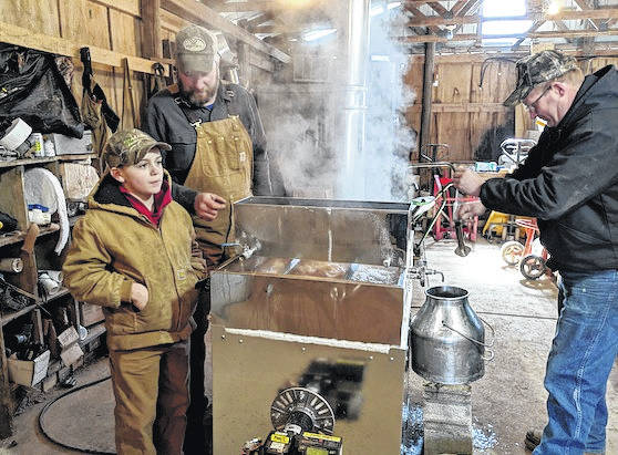 Lane Rizor, Jim Meimer and Jerry Korody by the small evaporator that cooks about eight gallons of maple syrup. Visitors look at the new large evaporator in the Sugar House at Pleiades Farm during an open house on March 10.