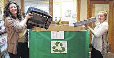 Hillary Scholz, youth services librarian, and Cieria Burgett, cataloger, add items to the recycling box at the library.