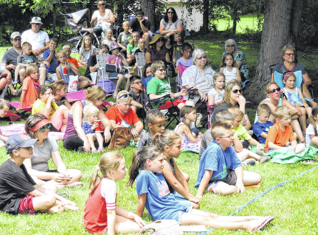 Families gather to enjoy a magic show during Selover Library's 2017 Summer Reading program.