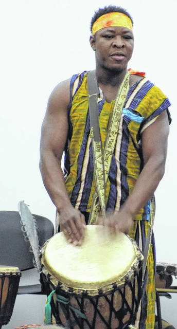 Sogbety Diomande playing a djembe.