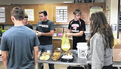 "Cardington's FFA motto, ""Living to Serve,"" was demonstrated when they served over 275 meals at the annual Spring Barbecue last month. The meal included two pork loins, cheesy potatoes from All Occasions Catering, a roll, a dessert and beverage. The meat was provided by Smithislers Meat and was prepared by Mr. Blankenship, Mr. Straley and Mr. Snodgrass. The Cardington FFA thanks everyone who purchased the meals and they hope to see everyone again at the Fall Barbecue. Liam Warren, Dylan Goodman and Skyler Streich Cardington FFA, serve up the pork barbecue dinner."