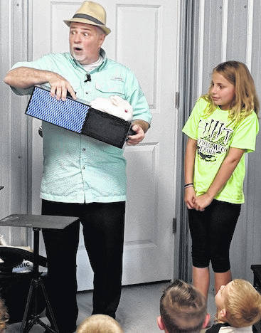 Selover Library patron Alexis Brown assists magical entertainer Greg Carson with his magic bunny Trixie on June 13 in Chesterville during Selover Library's Summer Reading program. Visit the library's Web site or Facebook page to find out about future programs.