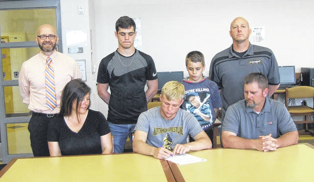 Conan Becker (front row, center) signs his letter of intent to wrestle for Kent State University while flanked by parents Anna and Michael. In the back row are Northmor high school principal Benjamin Bethea, brothers Conor and Cowin and Knight wrestling coach Scott Carr.