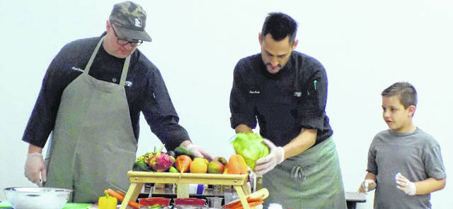 "Chef Chuck Johnson's team, ""Team Master,"" made a watermelon and apple salad complemented by plum juice and sage. Chef John Croke's team, ""Team Red,"" made fruit sushi. Shown are Johnson, John Croke and Marshall Hand."