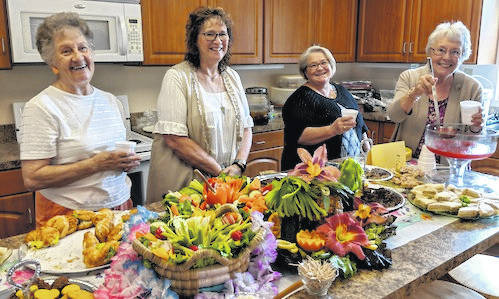 Wayside Club members served a colorful tropical luncheon at their 60th anniversary reception. From left: Doris McManis, Charlotte Benedict, Erica Grooms and Sue Quigley.