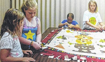 Children working on a blanket (one of several) to be sent to Haiti.