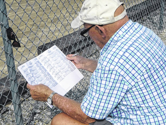 John Keller studies the harness racing program Tuesday afternoon.