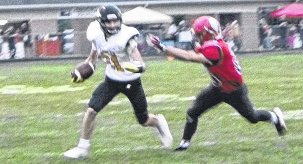 Colonel Crawford's Jordan Fenner tries to get around a Cardington defender Friday night. The Eagles overcame sloppy play to post a 28-12 win over the Pirates.
