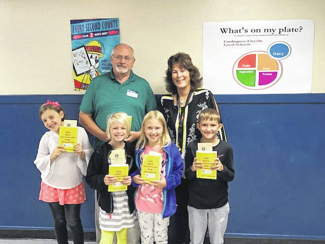 Gil Ullom, Cardington Rotary Club treasurer and Dawn Ruehrmund, Cardington third grade teacher. Also pictured are third grade students Cameron Romine, Lydia Levering, Cadence Fleming and Cyrus Linkous.