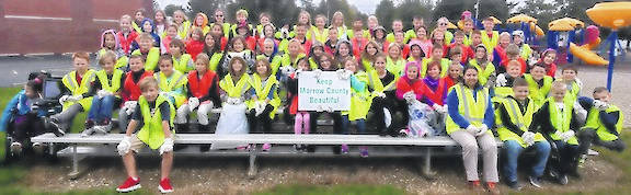 Cardington third graders with bags of trash they collected from their playground.