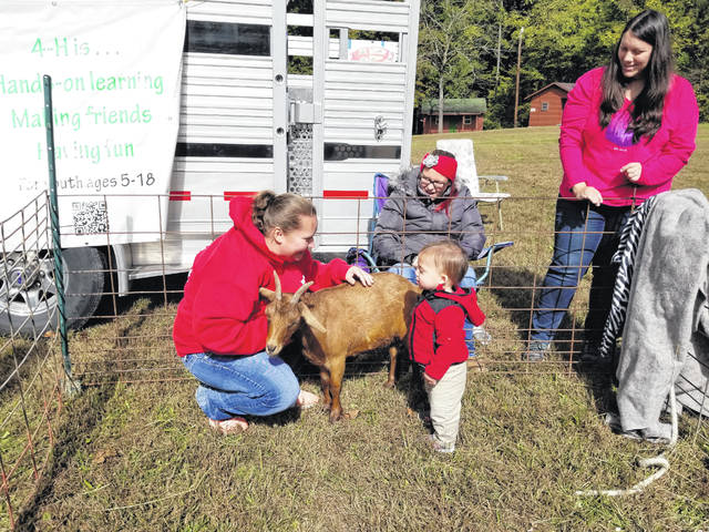 The Discover 4-H Club held a hands on learning petting zoo at the recent LMC Apple Butter Festival. Here Betty Gallagher, Fayth Gallagher and Shane White, who is petting the goat. Shane's mother, Laura White, looks on as he enjoys the animals.