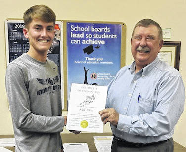 Kyle White accepts a certificate of recognition from board president Virgil Staley for his good deed in helping a teammate in distress at the Thill Cross Country meet.