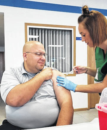 Jeremiah Woodmansee, Morrow County Paramedic EMT, focuses sharply as he receives his annual flu shot from Morgan Kocher, MCHD Public Health Nurse.
