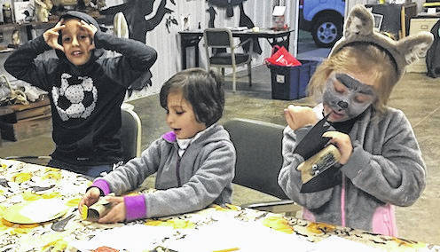 Children making animal crafts at the Night Skies event. From left: Ricky Edwards demonstrates looking at the sky, Jackie Edwards works on her owl craft and Emilee Hoffmaster came dressed up as a wolf.