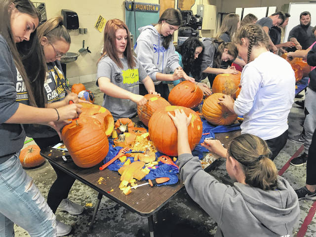Cardington FFA members carve pumpkins for Woodside Village residents.