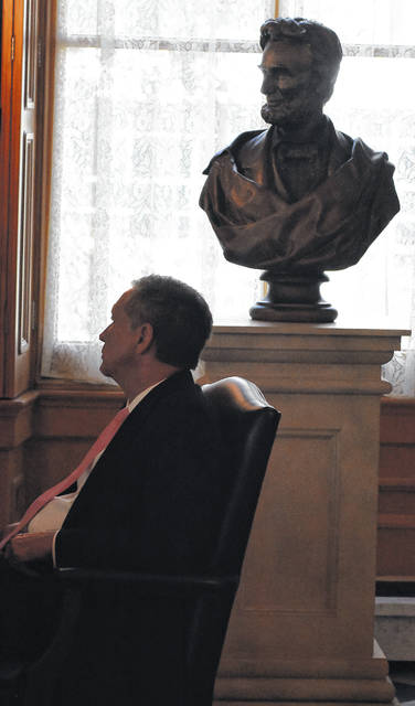 Gov. John Kasich answers questions in his office with a bust of Abraham Lincoln in the background in the governor's office.
