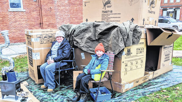 "Jessica Scott and her son Alex are sitting outside the cardboard home they put together on the Mount Gilead Square. They were the first of 11 who registered to camp out for the United Way project ""Shack City."""