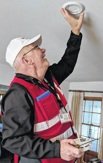 American Red Cross volunteer Dwight McFarland installs a smoke alarm in a home.