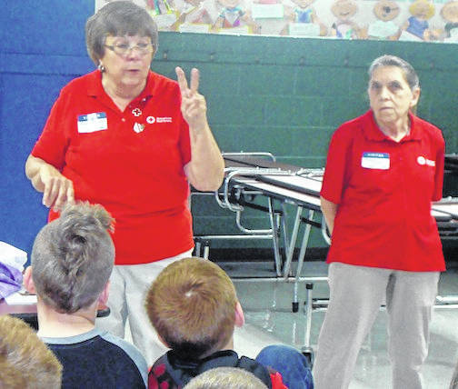 Rita Barton and Nancy Foos, American Red Cross and Gleaners members, speak to the Cardington-Lincoln third-grade students about the American Red Cross Pillow Case project.